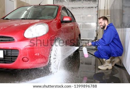 Worker cleaning automobile with high pressure water jet at car wash #1399896788