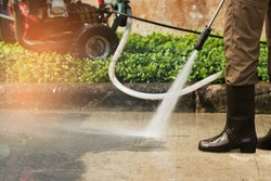 Worker cleaning driveway with gasoline high pressure washer splashing the dirt,professional cleaning services.High pressure cleaning,lower body.