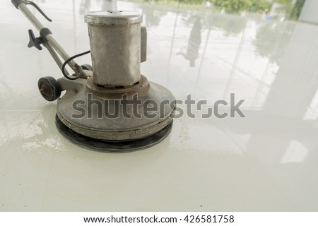 worker cleaning epoxy floor with machine and chemical cleaning by cleaning service capany