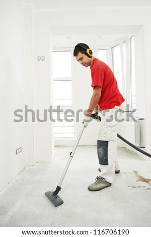 Worker cleaning floor with vacuum cleaner from industrial for Industrial concrete floor cleaning services