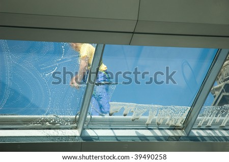 worker cleaning glass roof of modern building