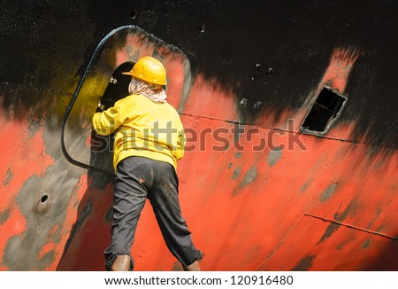 Worker cleaning side of ship at shipyard