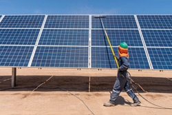 Worker cleaning solar modules in a Solar Energy Power Plant at an arid climate in Atacama Desert at Chile. Manual cleaning with a pole, water and a brush