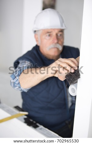 worker cleaning wall surface with a broomstick #702965530