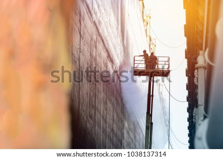 worker cleaning with ship by high pressure water ware equipment safety  harness for high work  under ship repair in floating dock minimal  monochrome concept with sun shines