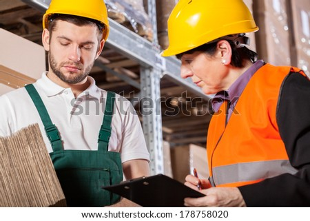 Worker consulting storage details with manager in warehouse - stock photo