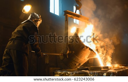 Worker controlling metal melting in furnaces. Workers operates at the metallurgical plant.