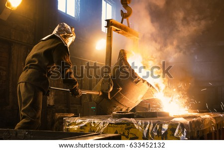 Worker controlling metal melting in furnaces. Workers operates at the metallurgical plant. The liquid metal is poured into molds. #633452132