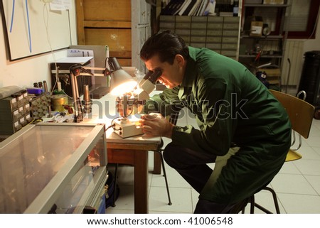 worker controlling quality at the microscope