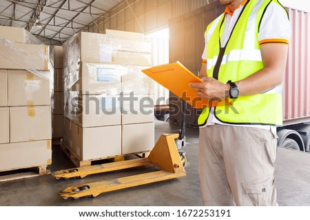 Worker courier holding clipboard inspecting checklist load shipment goods into a truck, Freight industry warehouse logistics transport,  forklift pallet jack and stack package boxes. Сток-фото ©