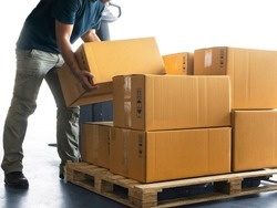 Worker courier lifting boxes stack on pallet, package, cardboard box, warehouse delivery service shipment goods, manufacturing warehouse.