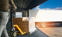 Worker courier unloading cargo pallet shipment goods, his using hand pallet  jack load into a truck, Road freight transport, Warehouse industrial delivery shipment  and logistics