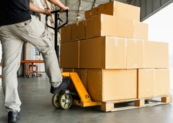 Worker courier unloading shipment goods, hand pallet truck and stack package boxes on pallet, warehouse delivery service transport and logistics.