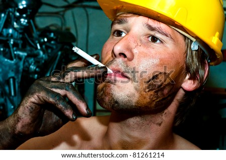 Worker covered in oil smoking