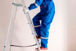 worker craftsman step up the ladder to repair home