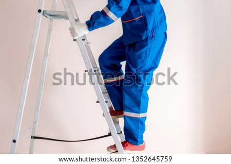 worker craftsman step up the ladder to repair home  stock photo