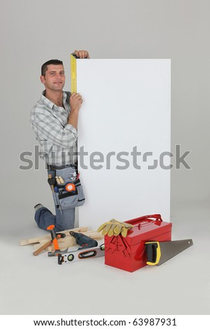 Worker crouching near a white sign