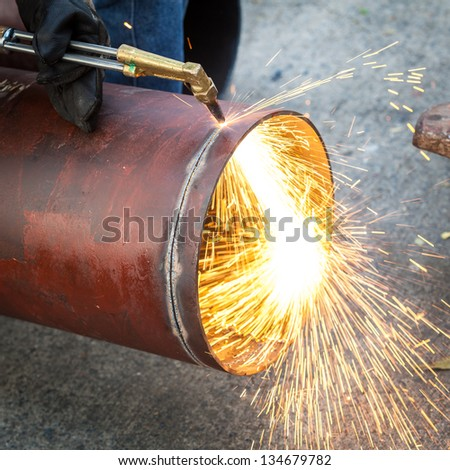 Worker cut big pipe with spark light