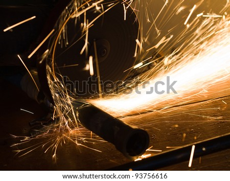 worker cuts a metal pipe by means of the abrasive tool