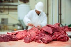 Worker cuts meat butcher handling cuts of prime choice cuts