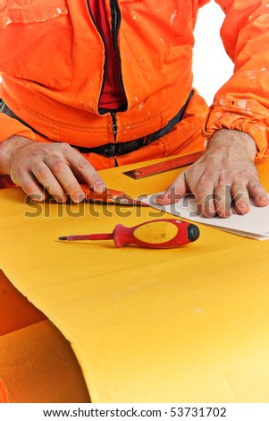 worker cuts the folded sheet of paper