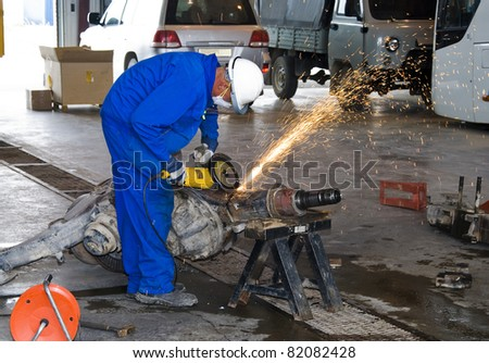 Worker cutting detail with many sharp sparks