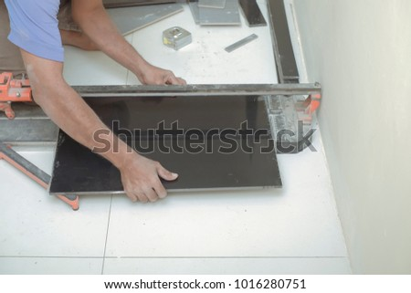 Worker Cutting Floor Tiles With Manual Cutter At Construction Site