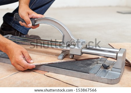 Worker cutting floor tiles with manual cutter - closeup
