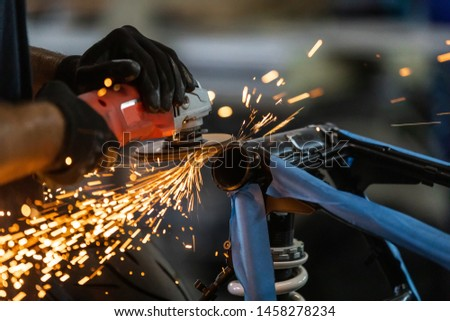 Worker cutting, grinding and polishing motorcycle metal part with sparks indoor workshop, close-up.