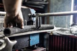 Worker, cutting hydraulic hoses in a metal workshop