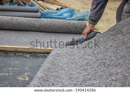 Worker cutting insulation material for basement wall, protection and drainage of walls and foundations