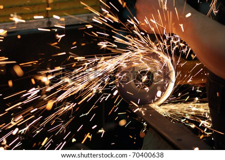 Worker cutting metal using angular grinding machine