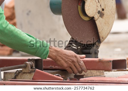 Worker cutting metal with grinder in construction site. Sparks while grinding iron