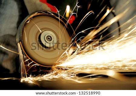 Worker cutting metal with grinder Sparks while grinding iron