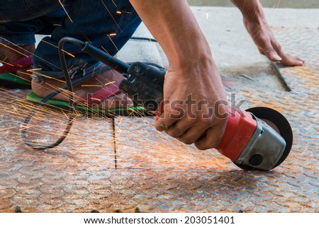 Worker cutting metal with grinder. Sparks while grinding iron