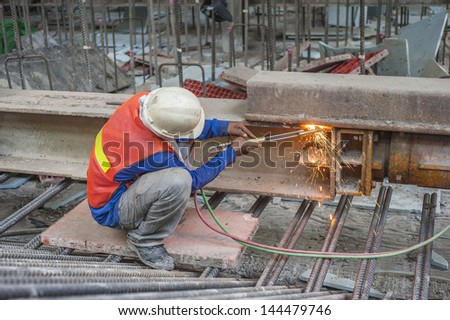 Worker cutting steel beam in a construction