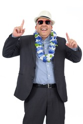 Worker dancing and partying. He is wearing a Hawaiian flower necklace and sunglasses. Carnival concept, joy, party and fun.