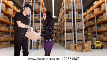 Worker delivering a parcel to young woman in a distribution warehouse
