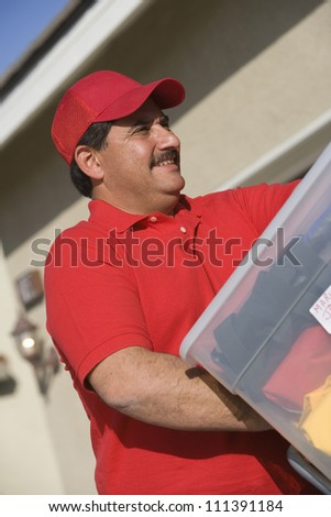 Worker delivering cardboard boxes into new house