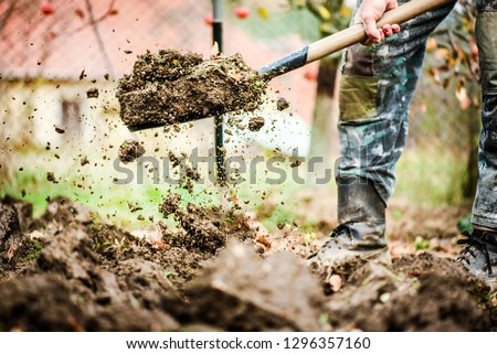 Photo of  Worker digs soil with shovel in colorfull garden, workers loosen black dirt at farm, agriculture concept autumn detail. Man boot or shoe on spade prepare for digging.