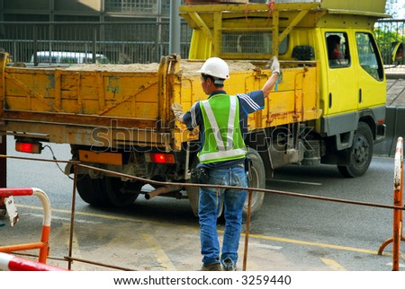 Worker directing a sand-filled dump truck at a construction site