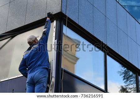 worker dismounts the window #736216591