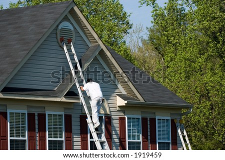 Worker doing home improvement climbs a ladder to the peak of a two story single family home.