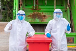 worker double like and tumb and upwear PPE protective clothing against corona virus of Infectious waste garbage collector truck loading waste and trash bin.