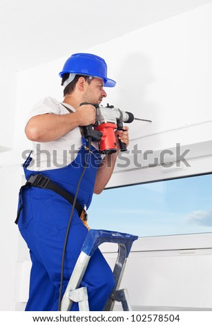 Worker drilling hole in the wall with power drill standing on ladder