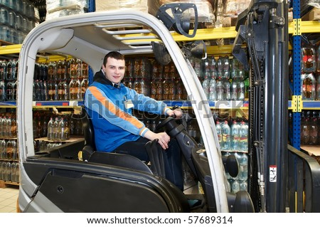 Worker driver of a forklift loader at food warehouse distribution works