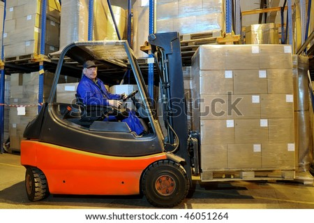 Worker driver of a forklift loader in blue workwear at warehouse with cardboard boxes on pallet
