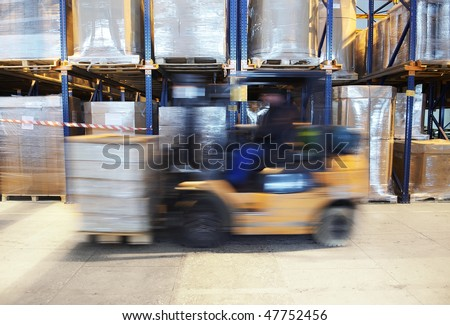 worker driving a forklift loader in warehouse with load on the pallet