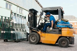 Worker driving forklift and loading glass constructions
