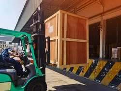 Worker driving forklift loading shipment carton boxes goods on wooden pallet at loading dock from container truck to warehouse cargo storage in freight logistics, transportation industrial, delivery